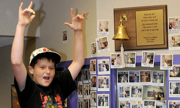 Picture of a boy ringing a bell to mark the end of his cancer treatment. Such ringing of bells is becoming more common in the NHS, though some patients object to it.