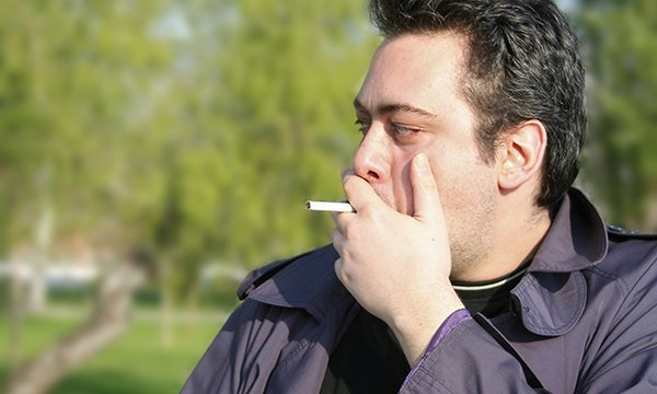man standing outside, smoking. A hospital trust has banned smoking on its site, even outdoors