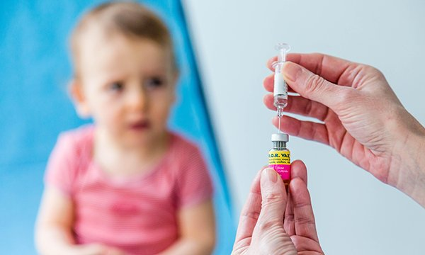 Nurse's hands seen preparing vaccine for child. MMR uptake is down, and measles cases in UK going up