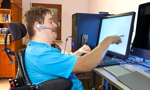 Image show young man with a learning disability using an adapted computer