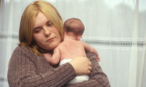 Picture show model depicting depressed young mother holding a baby. Support such as listening visits by health visitors to new mothers with mental health problems could be improved.