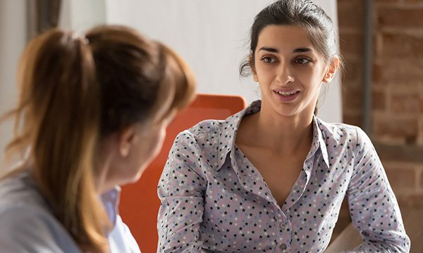 Image shows a social care manager talking to a member of staff