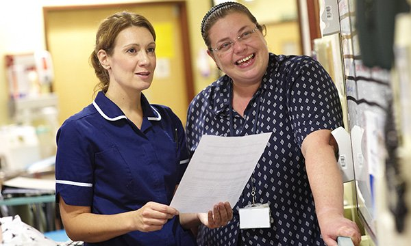 two nurses talk happily on the ward