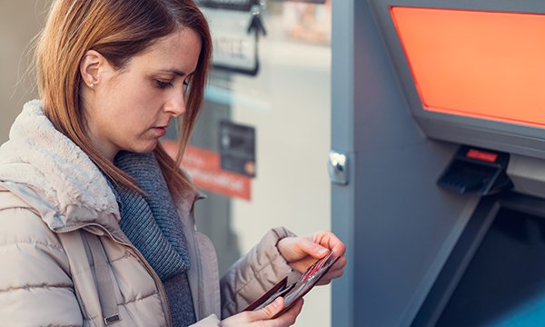 Young woman takes her bank card out at a cashpoint
