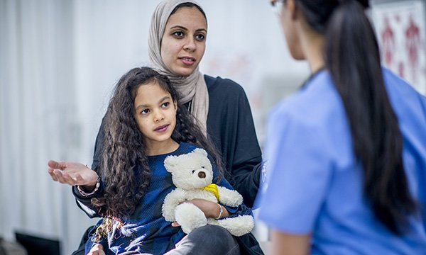 Picture shows a woman wearing a headdress holding a child while talking to a nurse. Great Ormond Street Hospital in London will host a study day on 14 November 2019 on working in a multicultural health service.
