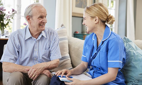 Picture shows a nurse doing a medicines review with an older man. A nurse-led monitoring tool that checks for adverse drug reactions could help curb overuse of mental health medicines in care homes, researchers say.