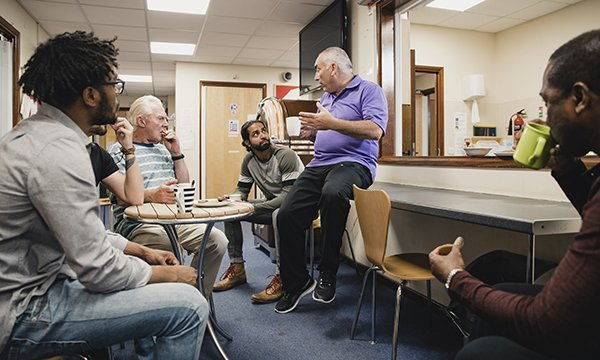 Picture shows a group of men talking to a mental health professional in a support group meeting. A community mental health framework for adults and older people will integrate mental health, physical health and social care services.
