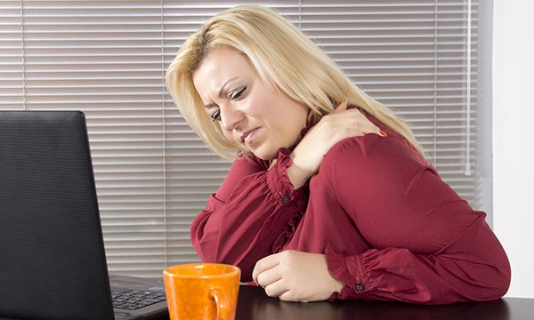 Picture shows a woman holding her shoulder to ease pain. The article stresses the need to raise awareness about coronary heart disease and heart attack, including gradual onset myocardial infarction, so that people know what symptoms to look out for.