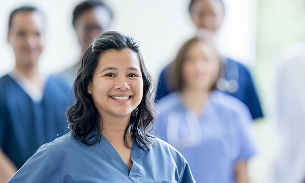 Picture shows a group of overseas nurses, with a young woman smiling in the foreground. The article says the international recruitment solution cannot be ignored.