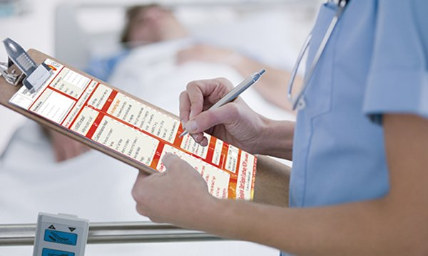 nurse holds clip board and completes paperwork to illustrate use of the Sepsis 6 tool
