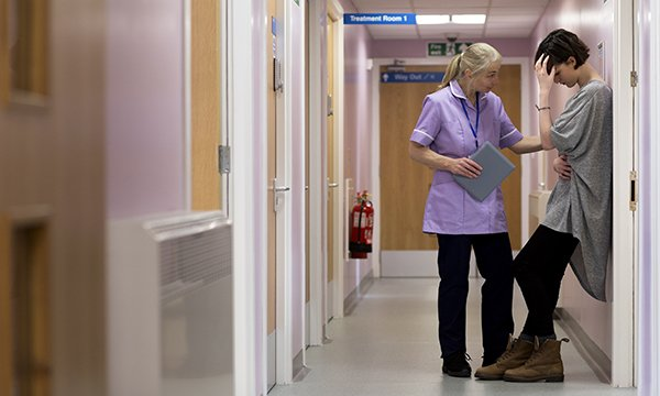 Picture of a hospital corridor where a medic is comforting a young woman. By walking in the shoes of carers whose loved ones are dying, teams of nurses are finding ways to improve support offered by their hospitals.