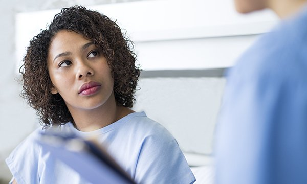 woman sitting in hospital gown looks up at healthcare professional