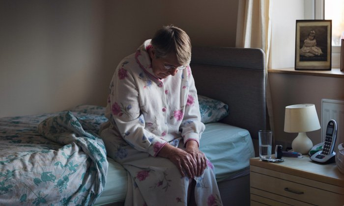woman sits in her dressing gown on the edge of her bed