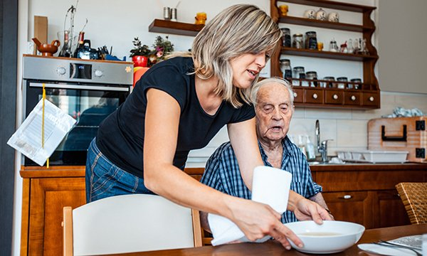 woman helps frail man to take a meal at a kitchen table