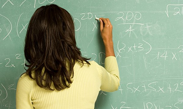 Woman undertaking maths calculation on a chalkboard