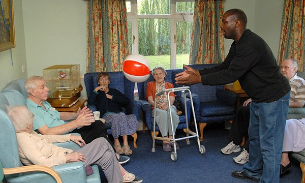 Picture shows a group of older people sitting in chairs while a younger man in the centre of the room throws one of them a beach ball. A four-year project will build data resource on treatment and services at care homes.