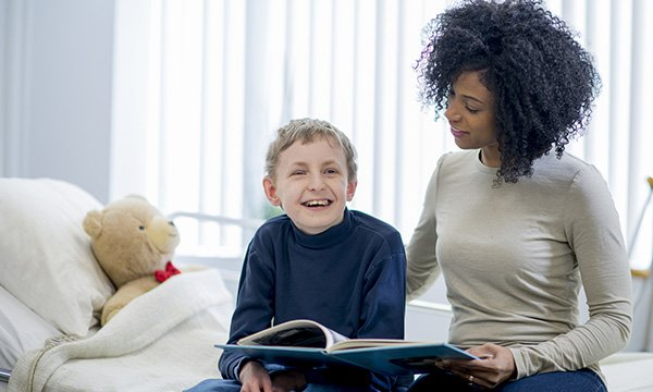 Picture shows a woman and a boy sitting on a hospital bed, reading a book together. Nurses interviewed about caring for children with learning disabilities in acute settings stressed the need to be adaptable and flexible