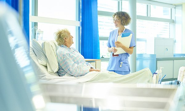 Picture shows a female medic chatting to an older woman who is sitting up in a hospital bed. The article says the nursing profession needs to debate whether intentional rounding is the best way to deliver care to patients.