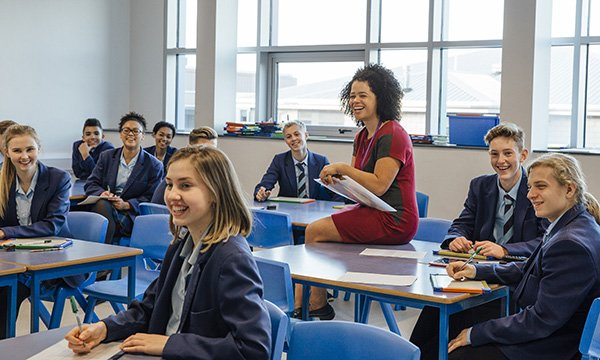 Image shows school teacher interacting with young people in a classroom lesson