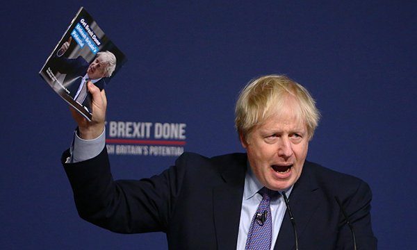 Prime minister Boris Johnson speaks at a podium, holding aloft the Conservatives' 2019 election manifesto