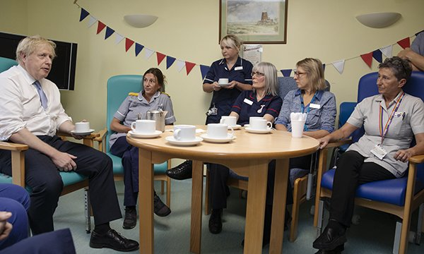 Boris Johnson sits around a table talking to nurses at West Cornwall Hospital