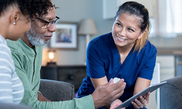Picture shows a community nurse at the home of an older man and his daughter. In this article Ian Bailey says the technology exists for multidisciplinary teams to instantly share updated patient records, and nurses must be given access to it.
