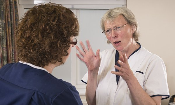 two nurses talking – one is gesticulating and looking angry