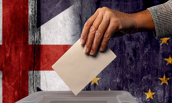 Stock image of a vote going in to a ballot box, with british and EU flags in the background