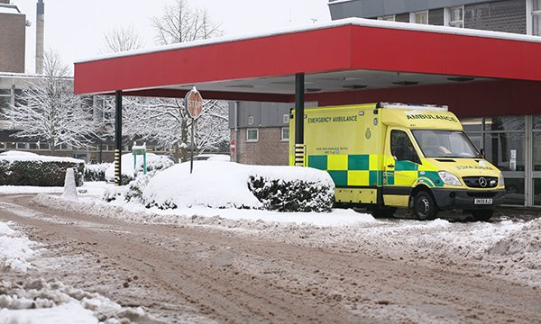 Image shows ambulance outside hospital emergency department in winter in the snow