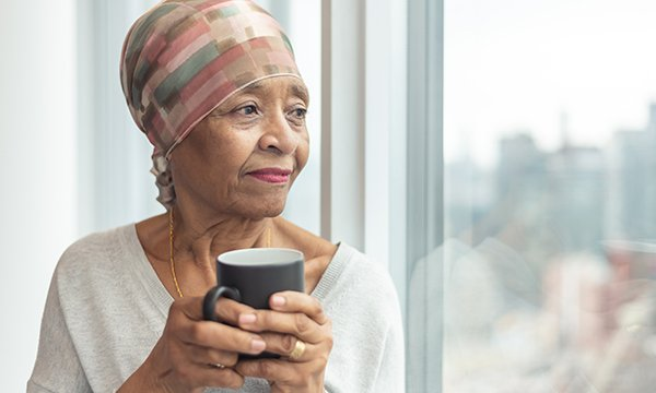 Picture of a lonely older woman looking out of a window