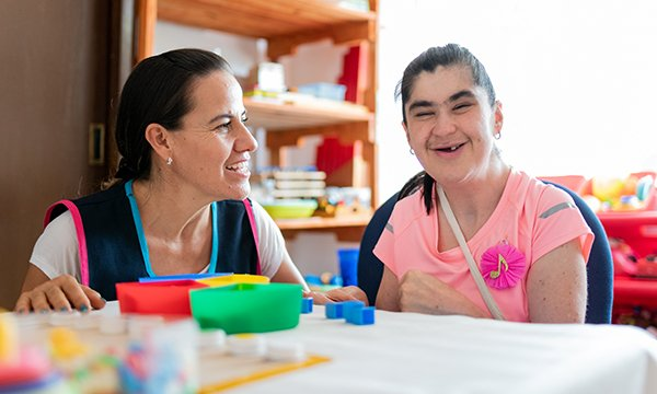 Picture shows mental health professional sitting at a table with a woman with Down's syndrome woman. A national framework in Ireland aims to provide person-centred services for people with learning disabilities and their families and carers.