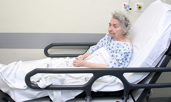 Older patient on trolley in corridor