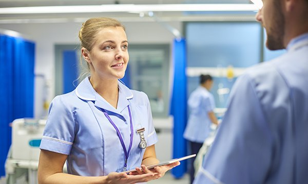 nursing student talks to colleague on a ward