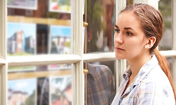 young woman looks through estate agent's window