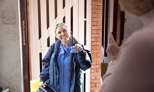 Picture shows a nurse displaying her name tag at a patient's front door. Scotland's integrated workforce plan is only a first step towards delivering commitments on district nursing.