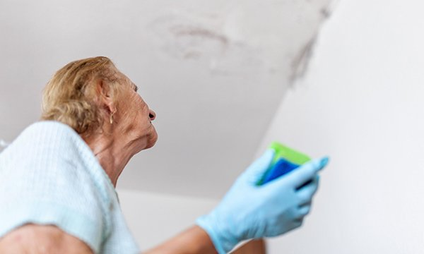 Picture shows a woman wearing household gloves and holding a cleaning sponge looking at patches of mould. Poor air quality in the home is linked to a range of health problems, and guidance from NICE suggests how to achieve improvements.