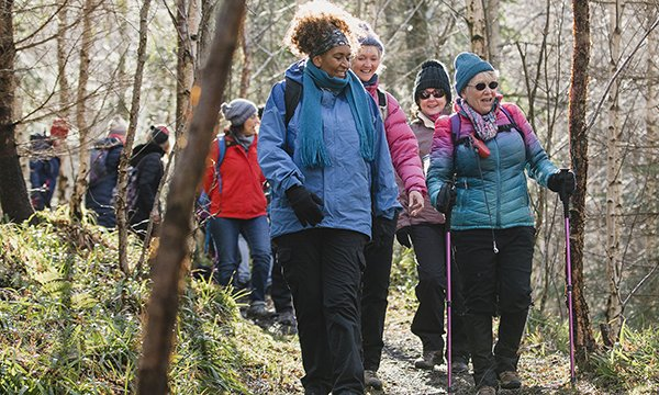 Picture shows a group of hikers going through a wood. Evidence shows physical exercise has a positive effect on patients before, during and after treatment.