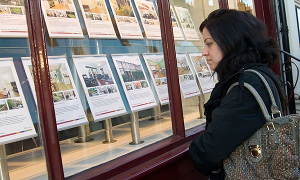 Woman looking at an estate agent's window
