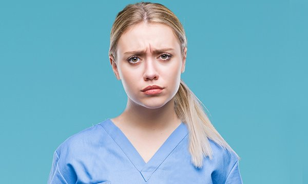 A worried-looking nursing student wearing scrubs