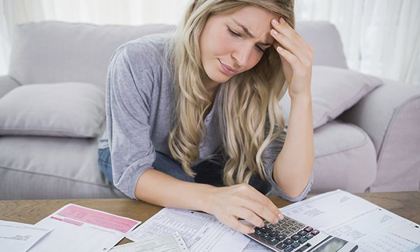 worried-looking woman sits on sofa at home, working with a calculator as she pores over financial statements