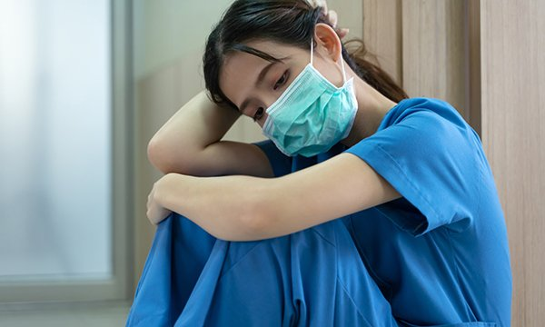 Nurse dressed in scrubs and face mask slumps and looks exhausted as nurse leaders employers to protect staff ahead of a second wave of covid-19