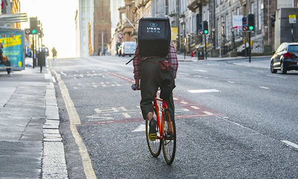 Picture shows a cyclist carrying a rucksack labelled Uber Eats
