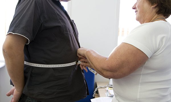 Obese nurse measures obese patient