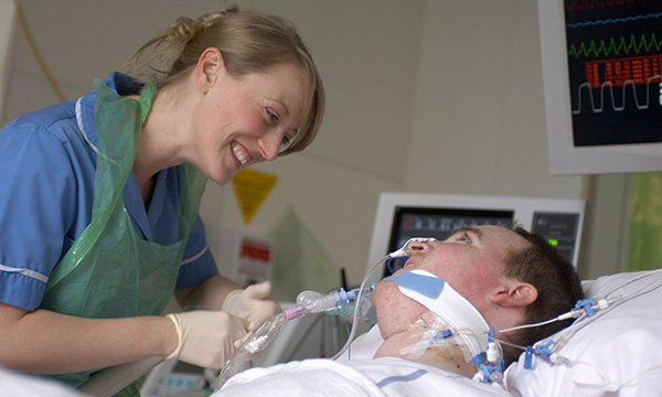 A staff nurse tends to a patient on a respirator in a hospital bed.