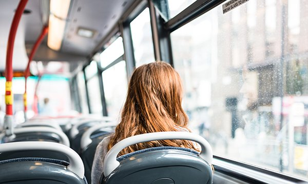 woman sits alone on top deck of a bus