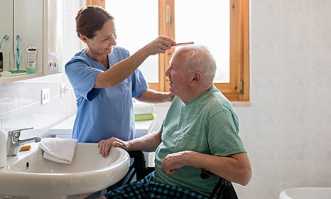 Nurse combing an older patient's hair