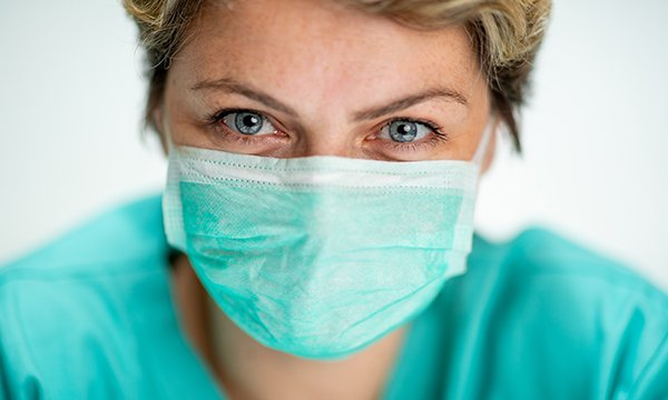 Nurse wearing a face mask – COVID-19 face coverings pose communication challenges for healthcare staff and people who are deaf or have dementia