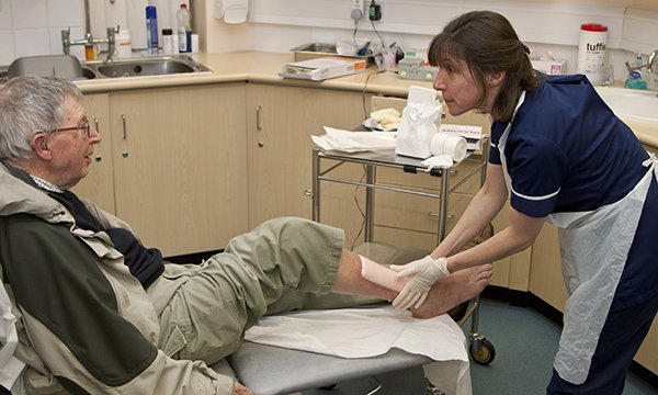 nurse care for man's leg wound in a practice setting