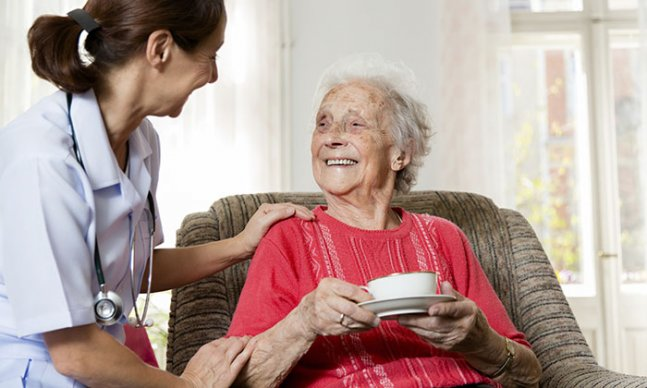 nurse sits beside a woman who is sitting in an armchair, holding a cup and saucer.They smile at each other