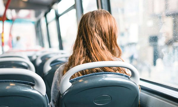 Image of a person sitting alone on a bus looking out the window, suggesting loneliness or sadness